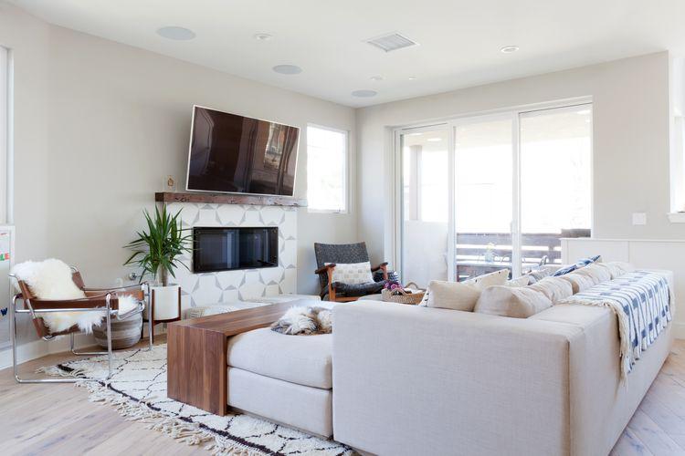 Living modern cu mobilier alb si televizor suspendat